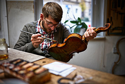 Violin maker in his workshop varnishing repaired violin - p300m1052842f by Dirk Kittelberger