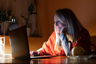 Smiling woman listening to video call on laptop while sitting by table at home - p300m2240470 by Eloisa Ramos