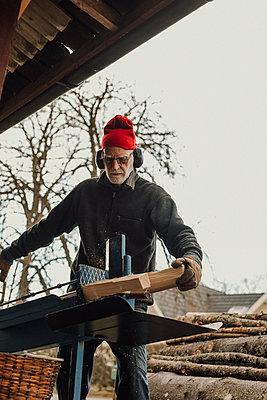 Senior man sawing wood - p312m2191244 by Jennifer Nilsson