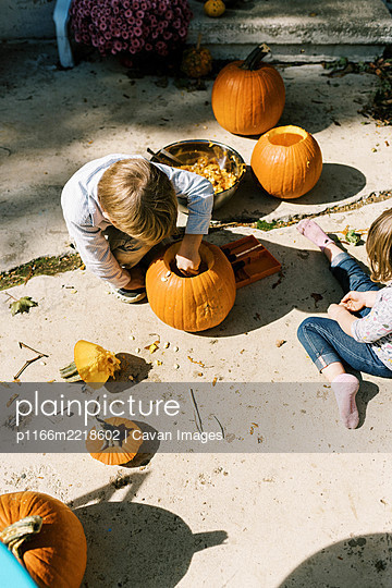 Two children carving out pumpkins for halloween on their patio - p1166m2218602 by Cavan Images