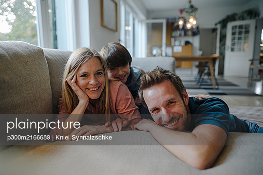 Happy family lying on couch, smiling at camera - p300m2166689 by Kniel Synnatzschke