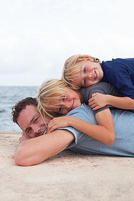 Die Söhne machen es sich auf Papas Rücken gemütlich - p045m2028555 von Jasmin Sander