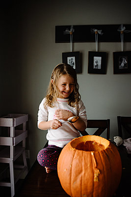 Little girl carving a pumpkin at home for halloween - p1166m2269344 by Cavan Images