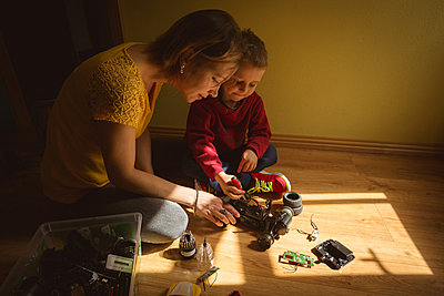 Mother and son repairing toy car in bedroom - p1315m2018460 by Wavebreak