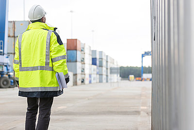 Man wearing safety jacket at container port - p300m1028824f by Milton Brown