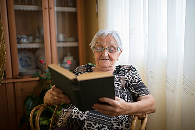 Senior woman reading a book at home - p300m1188391 by Ramon Espelt
