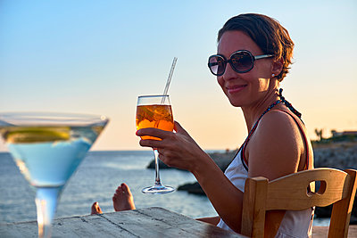 Italy, Santa Caterina, portrait of relaxed woman toasting with glass of Spritz at sunset - p300m1505578 by Dirk Kittelberger