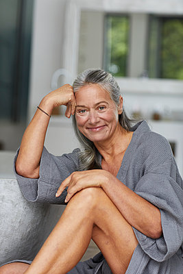 Beautiful mature woman leaning by bathtub in bathroom - p300m2241255 by Maya Claussen