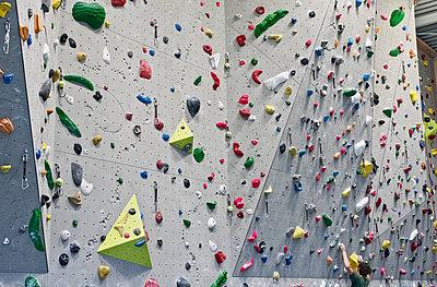 Man scaling rock wall - p318m2087183 by Christoph Eberle