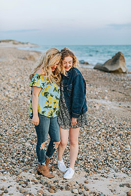 Two young women hugging on beach, Menemsha, Martha's Vineyard, Massachusetts, USA - p924m2058126 by Lena Mirisola
