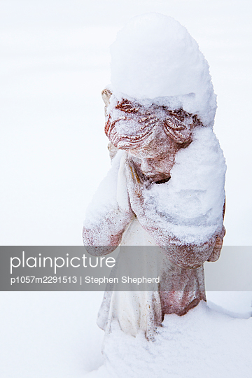 A small statue of an angel praying in a grave yard and covered in snow in the middle of winter. - p1057m2291513 by Stephen Shepherd