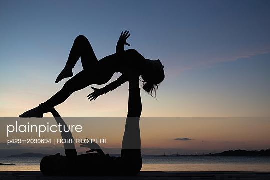 Women practising acro yoga at seaside - p429m2090694 by ROBERTO PERI