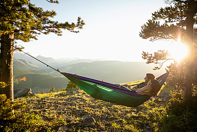 Serene couple relaxing in hammock on sunny, idyllic remote mountain hilltop, Alberta, Canada - p1192m2016579 by Hero Images
