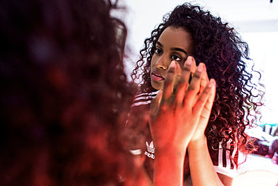Schöne junge Frau schaut sich im Spiegel an und berührt diesen mit ihrer Hand  - p1301m1441497 von Delia Baum