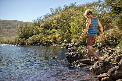 Junger Mann geht über Steine am Flussufer - p1355m1574218 von Tomasrodriguez