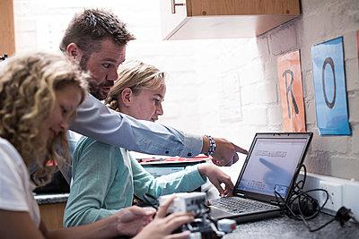 Teacher talking to schoolgirls with laptop in robotics class - p300m1053085f by zerocreatives