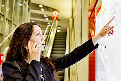 Germany, Cologne, young woman on the phone looking at city map in underground station - p300m1549394 by Jan Tepass