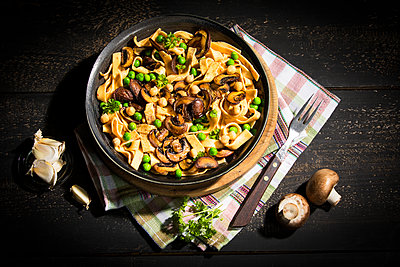 Ribbon noodles with Crimini Mushrooms, peas and chickpeas - p300m2080972 by Roman Märzinger