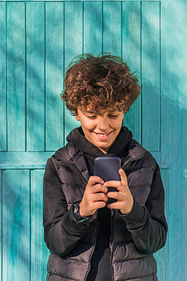 Smiling boy using cell phone outdoors - p300m2160006 by Javier De La Torre Sebastian