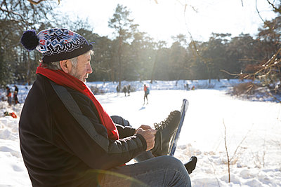 Senior man wearing ice skate while sitting on snow during winter - p300m2281871 by Frank van Delft