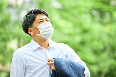 Young Japanese businessman wearing mask in the hot Summer downtown Tokyo - p307m2261311 by Naoki Morita