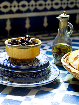 Black olives in ceramic bowl with blue and white plates and vinaigrette, Morocco, North Africa - p349m2167703 by Polly Wreford