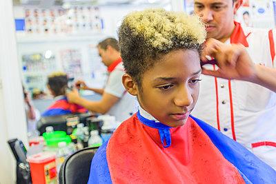 Hairdresser cutting teenage boy's hair in barbershop - p924m1422812 by Sue Barr