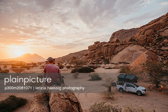 Namibia, Spitzkoppe, friends sitting on a rock watching the sunset - p300m2081071 by letizia haessig photography