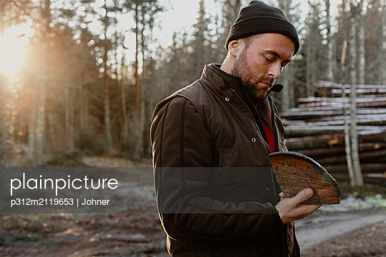 Man holding piece of log - p312m2119653 by Johner