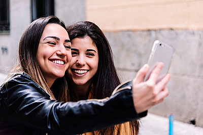 Beautiful Lesbian Couple Taking A Self Portrait At The Street. LGBT. - p1166m2165947 by Cavan Images