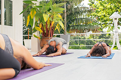 Two women and a man practicing yoga on terrace - p300m1588113 by Mosu Media