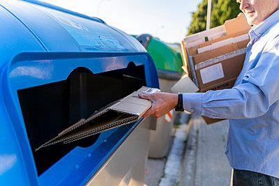 Senior man recycling cardboard in paper bank - p300m2113967 von VITTA GALLERY