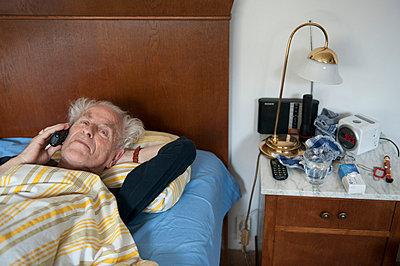 Alter Mann telefoniert im Bett - p896m836013 von Sabine Joosten