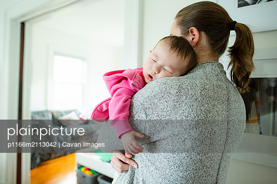 Baby girl sleeps on mom's shoulder while being held at home - p1166m2113042 by Cavan Images