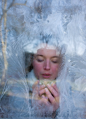Woman drinking a hot drink behind a window covered with frost flowers - p1231m1043093 by Iris Loonen