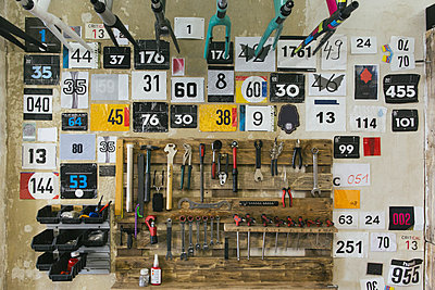 Numbers and tools hanging at the wall in a workshop - p300m1113403f by Julien Balmer