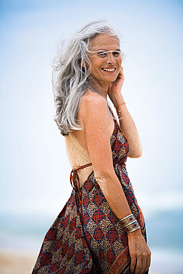Portrait of smiling senior hippie woman with sandy back on the beach - p300m2083829 by Steve Brookland