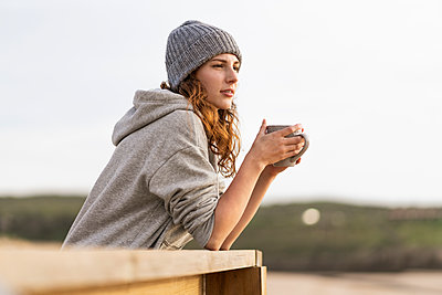 Woman wearing knit hat having coffee while leaning on railing - p300m2286962 by Steve Brookland