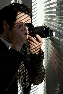 A man looking through blinds with a camera - p3017852f by Marco Baass