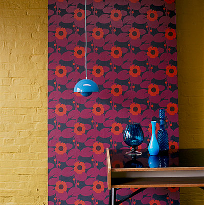 Panel of patterned wallpaper against a painted brick wall side table and home wares - p349m695171 by Emma Lee