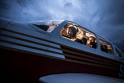 Low angle view of mid adult man flying aeroplane with friend sitting behind at dusk - p426m811423f by Katja Kircher