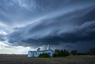 Supercell thunderstorm looms behind country church, Tatum, New Mexico, USA - p429m1494404 by Chris Kridler