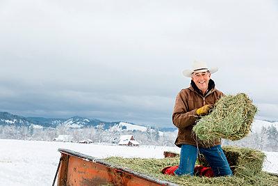 Caucasian farmer hauling hay in snowy field - p555m1312064 by Inti St Clair