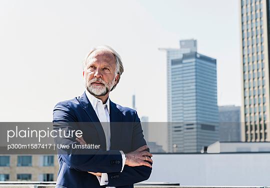 Serious mature businessman in the city looking around - p300m1587417 von Uwe Umstätter