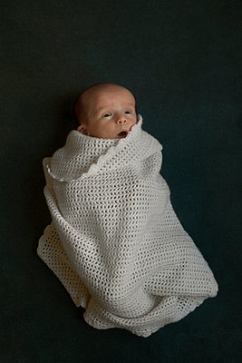 Surprised one month newborn wrapped in blanket - p1028m1031070 by Jean Marmeisse