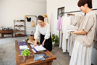 Two Japanese women standing in a small fashion boutique, arranging T-Shirts on a coffee table. - p1100m2146457 by Mint Images
