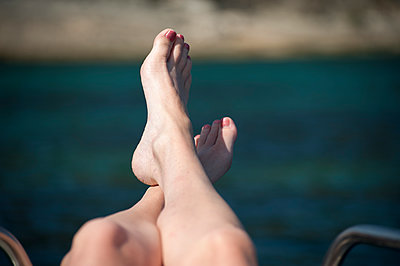 A woman's crossed lower legs and feet on the railing of a boat. - p1433m1529104 by Wolf Kettler