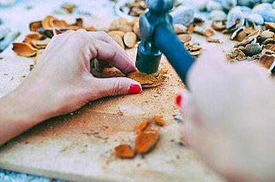 Hands of woman breaking almond husks with hammer - p300m2221539 by Kiko Jimenez