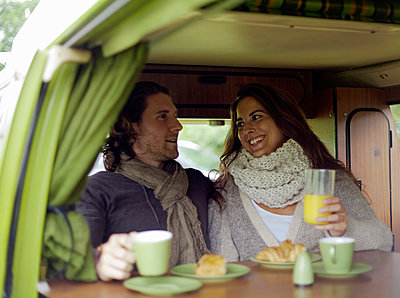 Woman talking with man while having juice in camper van - p300m2250221 by LOUIS CHRISTIAN