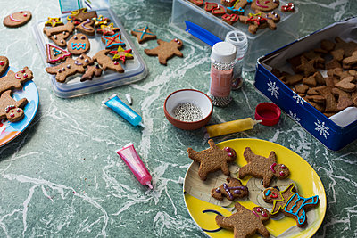 Various gingerbread cookies and decorating items on floor at home - p301m1579844 by Tobias Titz